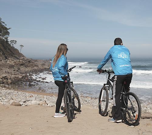 Dos personas en bicicleta en la playa de meron - Empresa Stass Actividades