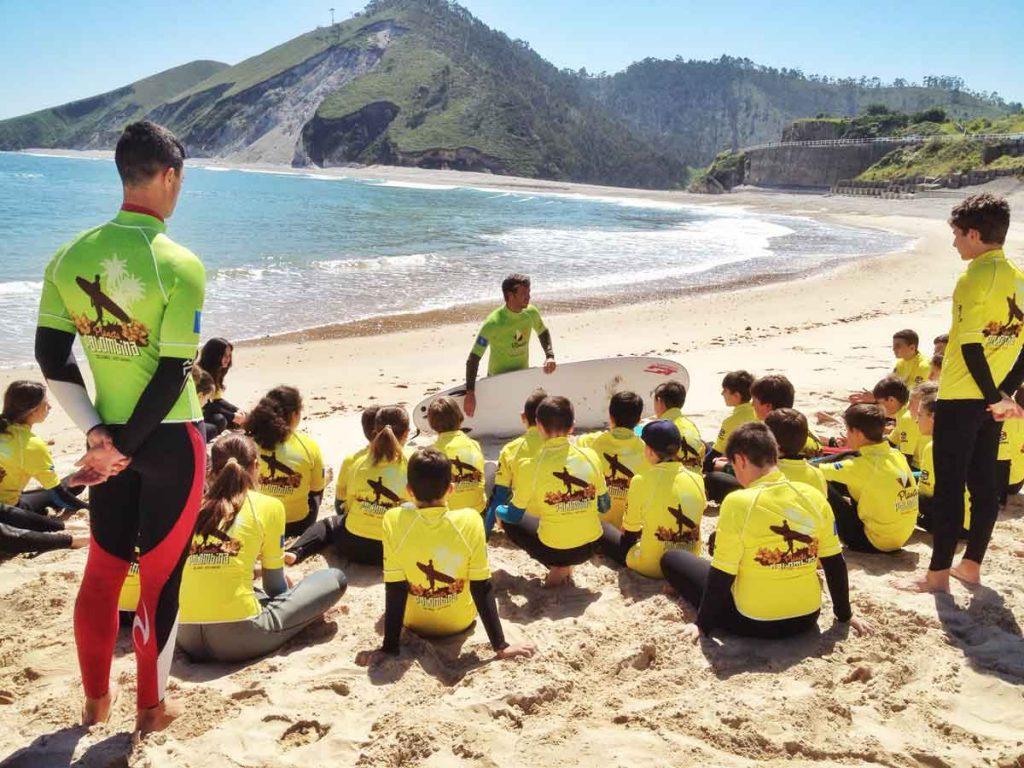 Grupo de niños en un curso de surf en una playa de llanes - Turismo Activo